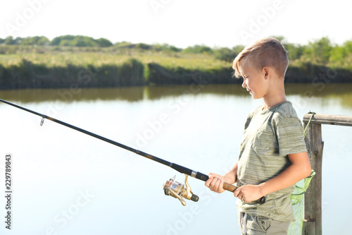 Little boy fishing alone on sunny day