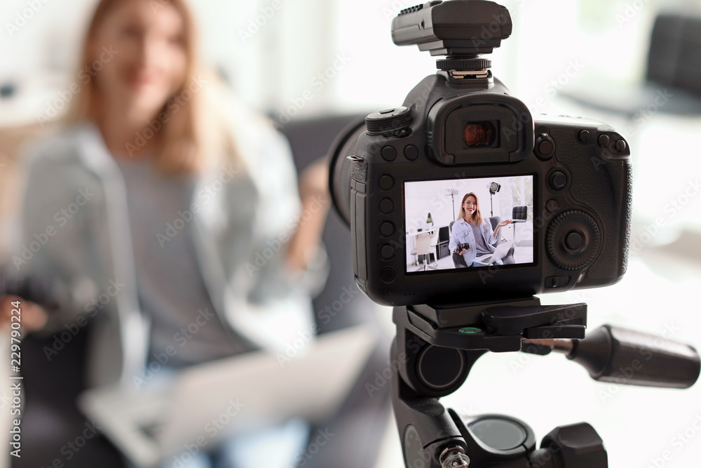 Fototapety, obrazy: Photo blogger recording video indoors, selective focus on camera display. Space for text
