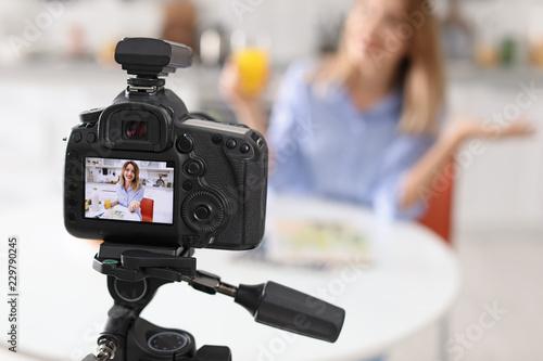 Fototapeta Food blogger recording video in kitchen, focus on camera display. Space for text obraz na płótnie