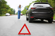 Emergency stop sign and woman near broken car on background
