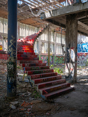 Fototapeta na wymiar Stairs leading up to another floor in an old abandoned building or factory, completely destroyed and vandalized, painted with colourful graffiti street art