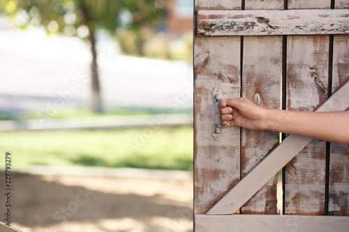 Woman opening old wooden door, closeup of hand