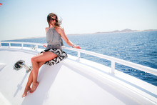 The Girl In A Black And White Dress In A Geometric Strip. Dissolved Hair. Journey On Boat On The Red Sea In Egypt. Brunette On The Trip. Fashion Photo Shoot