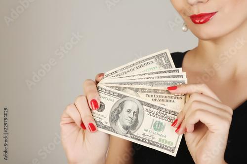 Fotografía  Women holds a pile of money on a gray background.