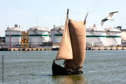 An ancient boat with sails on the background of a port oil terminal