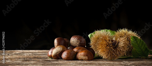Fotomural Chestnuts and chestnut bur on wooden table.