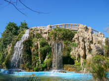 Artificial Waterfall With A Bridge Over Stone In The Park Parque Genovés In Cádiz, Spain