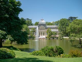 Palacio de Cristal - Glass Palace seen from across a pond in a public park in Parque de Retiro, Madrid, Spain, old historical building in a garden