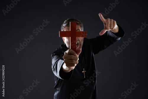 Fotografía  Priest holding cross of wood praying
