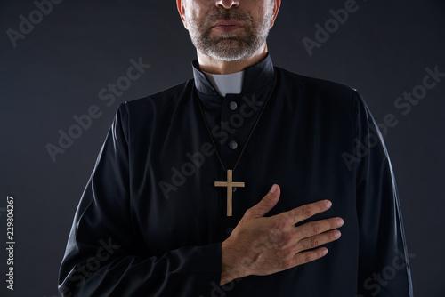 Priest hand in heart gesture with cross Wallpaper Mural