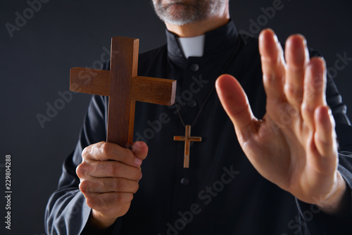 Photo Priest holding cross of wood praying