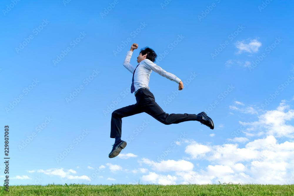 Fototapeta 青空をバックにジャンプするYシャツ姿の若いビジネスマン1人。元気・パワー・喜び・挑戦イメージ