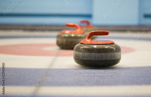 two granite curling rocks on the ice