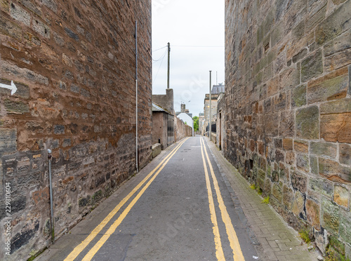 narrow street with high stone walls