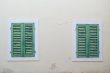 Two Windows Are Closed By Green Shutters Against A Beige Wall.