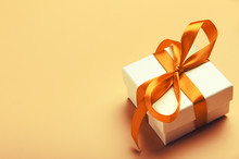 White Gift Box With Orange Bright Ribbon On Yellow Background. Beautiful Gift For The New Year, Christmas, Birthday. Copy Space