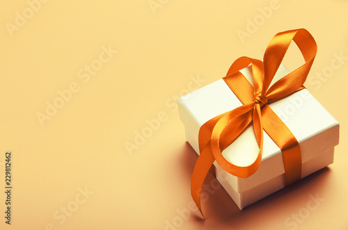 Photo  White gift box with orange bright ribbon on yellow background
