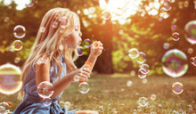 Portrait Of A Cheerful Girl Blowing Soap Bubbles