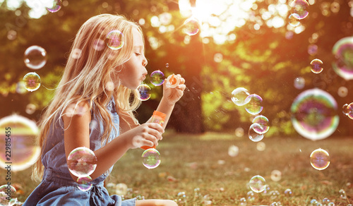 Tuinposter Artist KB Portrait of a cheerful girl blowing soap bubbles
