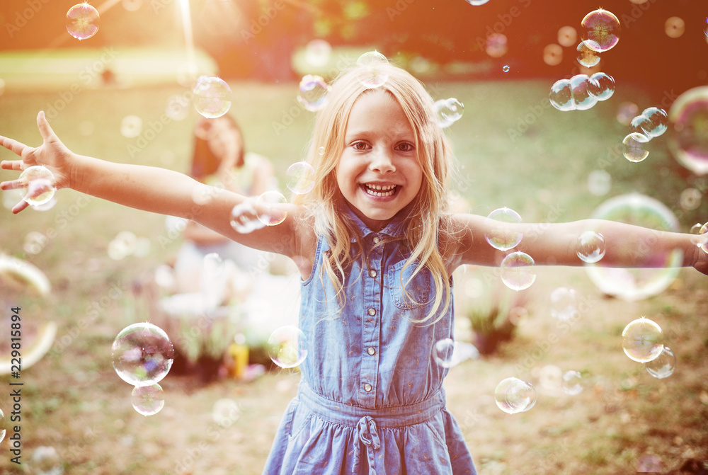 Fototapety, obrazy: Cheerful little girl enjoying bubble blowing