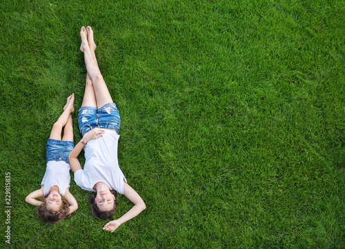 Acrylic Prints Artist KB Conceptual portrait of a mother relaxing with daughter on a fresh, green lawn