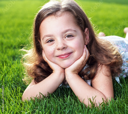 Acrylic Prints Artist KB Closeup portrait of a cute little girl lying on a fresh lawn