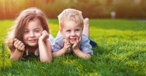 Tuinposter Artist KB Cheerful siblings relaxing on a fresh lawn