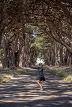 Caucasian Female Raises Arms Up At The Cypress Tree Tunnel On Point Reyes National Seashore In Marin County In Northern California