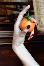 A Womans Hand Holding A Small Christmas Orange Between Her Thunb And First Finger