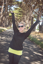 Artistic Angle Of Blonde Female Raises Arms Up At The Cypress Tree Tunnel On Point Reyes National Seashore In Marin County In Northern California