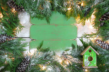 Blank Antique Rustic Green Sign With Christmas Tree Garland, Lights And Birdhouse Handing On Snowy Door; Holiday Background With Copy Space