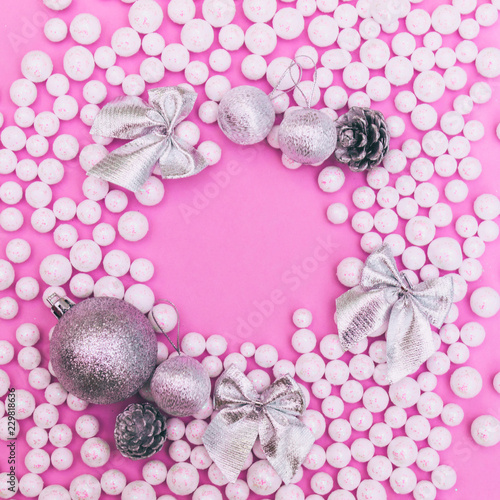 Fototapety, obrazy: Frame of Christmas bauble decorations with white and silver glitter balls and fir cones on pink background. Winter holidays concept