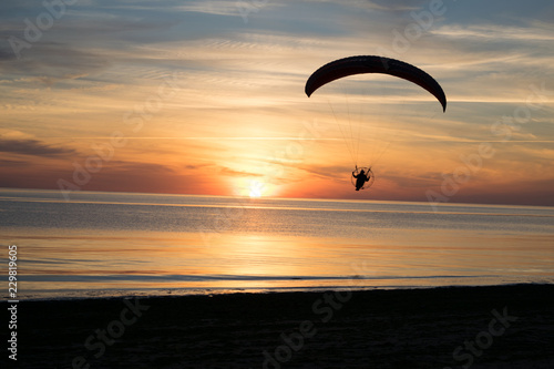 Paraglider over the sea at sunset.