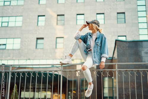 Fotografía  Pretty girl sits on the fence railing in a European city enjoyin