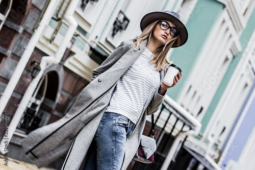 fototapeta na lodówkę Coffee on the go. Stylish and young woman in coat and hat drinking coffee outdoors. Beautiful hipster girl in modern urban outfit walking city streets with paper cup of coffee. City fashion concept