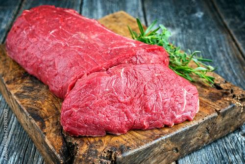 Foto op Aluminium Vlees Rohes Roastbeef mit Kräutern angeboten als closeup auf altem rustikalen Schneidebrett