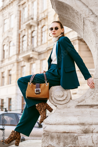 Outdoor full body fashion portrait of young woman wearing sunglasses, white turtleneck, blue suit, blazer, trousers, leopard print ankle boots, holding suede bag, posing in street of european city