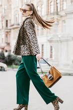 Outdoor Full Body Fashion Portrait Of Young Beautiful Fashionable Woman Wearing Sunglasses, Leopard Print Blazer, Boots, Green Trousers, Holding Brown Suede Bag, Walking In Street Of European City