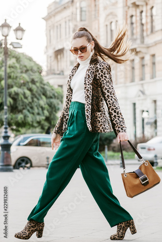 Outdoor full body fashion portrait of  fashionable woman wearing sunglasses, white turtleneck, leopard print blazer, boots, green trousers, holding brown suede bag, walking in street of european city
