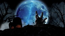 Zombie Hand Emerges From The Grave Amid Halloween Pumpkins And Flying Bats And The Blue Moon