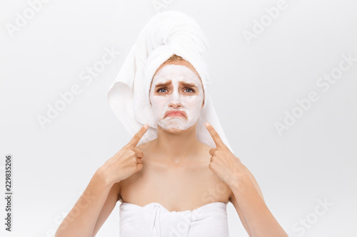 Unhappy beautiful young woman with white clay face mask