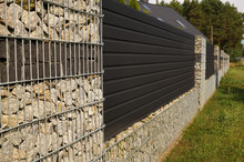 A Modern Wall. A Fragment Of A Long Fence Of A House Made With The Help Of Gabions.