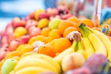 Closeup Of Fresh Ripe, Yellow Bananas, Orange Oranges In Street Market Display In Italy During Summer, Bokeh Background
