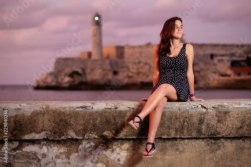 Beautiful hispanic girl sitting on the Malecon seawall at sunset in Havana Canvas Print
