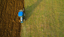 Top View Of The Tractor That Plows The Field. Aerial View Of A Tractor Ploughing Plowing Field