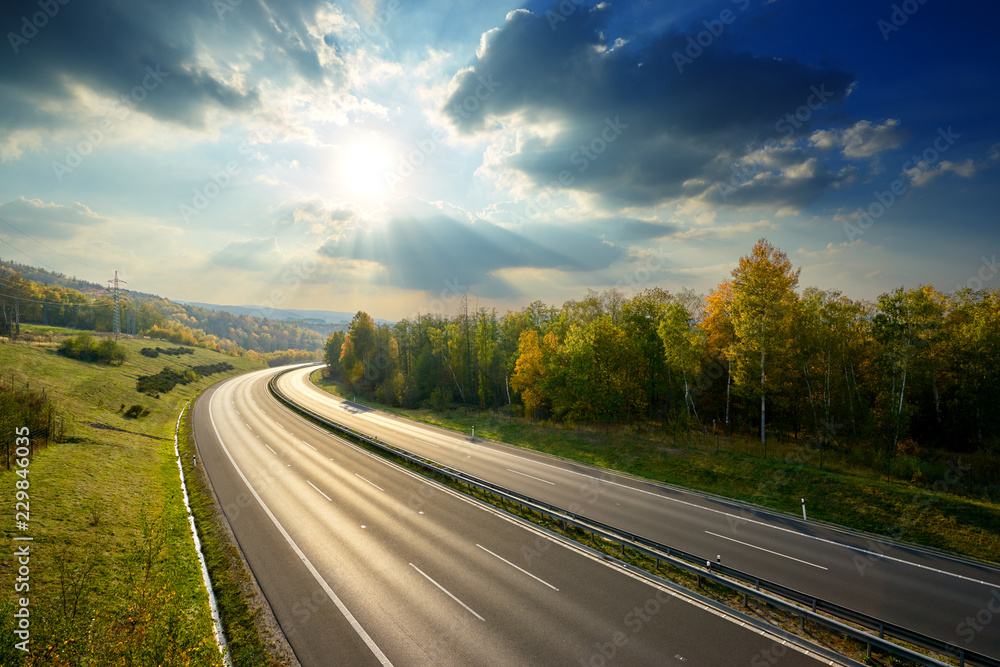 Fototapety, obrazy: Empty asphalt highway between deciduous forest in autumn colors under the radiant sun and dramatic clouds. View from above.