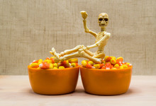 Halloween Skeleton Sitting On Top Of Two Orange Bowls Filled With Candy Corn On A Wooden Table Against A Curtain With Copy Space