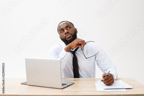 Fototapety, obrazy: thoughtful young african american businessman working on laptop computer