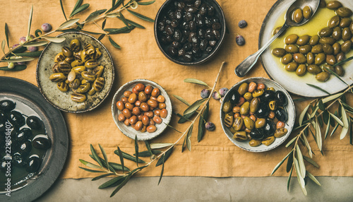 Flat-lay of various kinds of Mediterranean pickled olives in plates and bowls and olive tree branches on yellow linen cloth, top view. Mediterranean meze appetizer