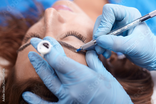 Fotografie, Obraz  microblading close-up, hands adding pigment to eyebrows.